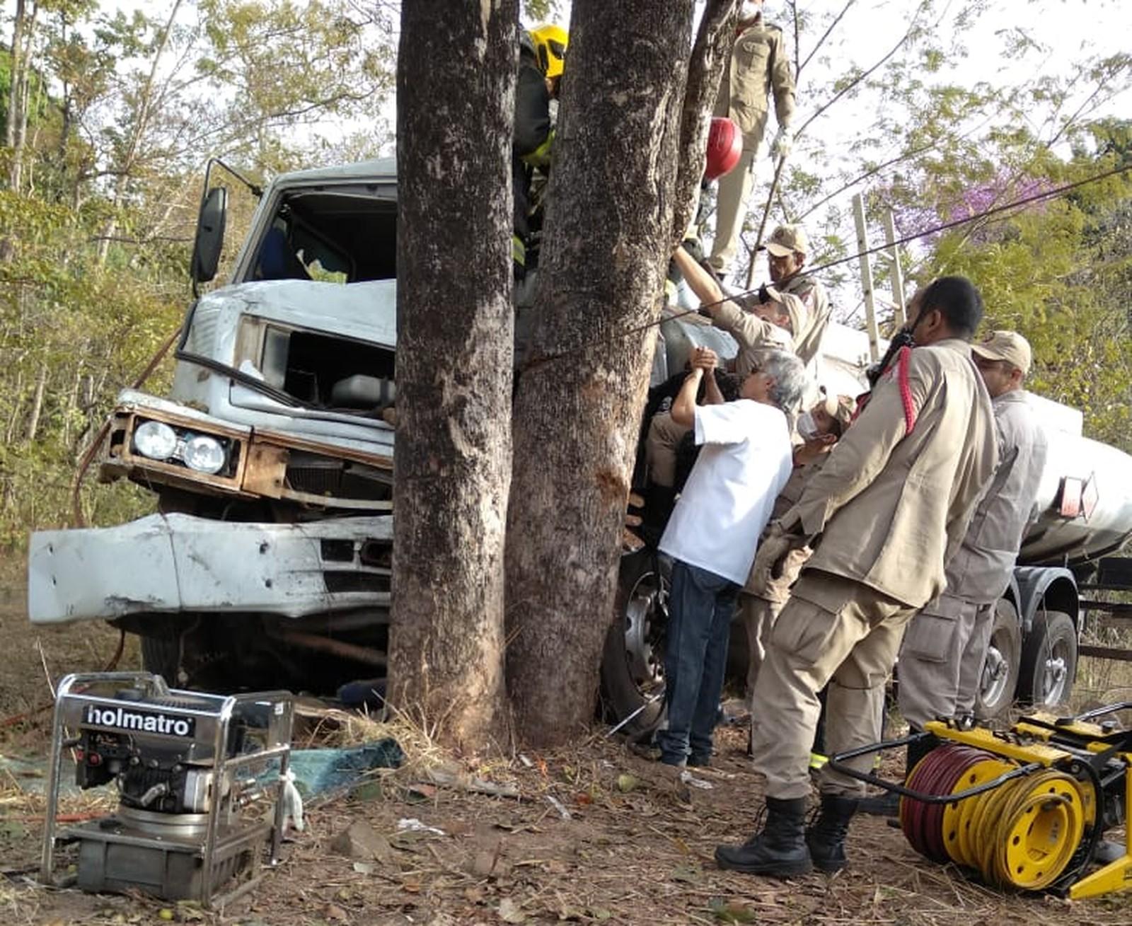 Caminhão-tanque bate em árvore e motorista fica preso à ferragens